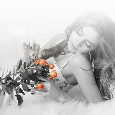 Красивая девушка лежа на белой кровати с цветами стоковые